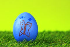 Easter egg. Easter decoration from single, painted blue, Easter egg with butterfly motif in green artificial turf Royalty Free Stock Photo