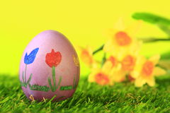 Easter egg. Painted with brightly colored flowers, in the background blurred daffodils Royalty Free Stock Images