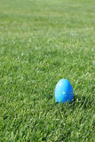Easter Egg 6. A blue plastic Easter egg with yellow polka dots on the grass - shallow DOF on egg royalty free stock photo