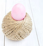 Easter egg and ball of hemp rope on wooden background Royalty Free Stock Photo