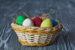 Easter egg basket with colored eggs Vintage gray wood background. Stock Images