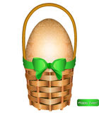 Easter egg in a basket with green bow. Royalty Free Stock Photography