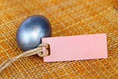 Easter egg and blank paper tag on bamboo weave sheet. Stock Image