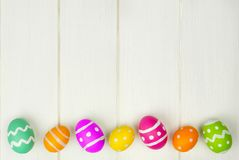 Easter egg border on white wood. Colorful Easter egg bottom border against a white wood background Royalty Free Stock Images