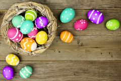 Easter egg border on wood. Easter egg border with nest over an old wood background royalty free stock photography