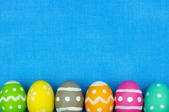 Easter egg bottom border over blue burlap background Royalty Free Stock Images
