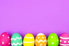Easter egg bottom border over purple paper background Royalty Free Stock Photography