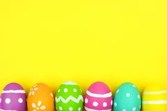 Easter egg bottom border over yellow paper background Stock Photos
