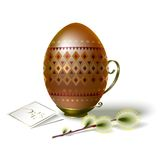 Easter egg with brown ornament and sprig of willow. Easter egg dark-gold with beautiful brown geometric ornament on vintage metal stand with handle Stock Images