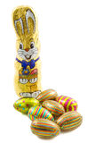 Easter egg bunnie. Chocolate bunnie with chocolate eggs in foil isolated over white Royalty Free Stock Photo