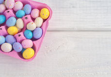 Easter Egg Candies in a Pink Egg Carton on Rustic White Board Background with space or room for text, copy, or words Royalty Free Stock Images