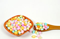 Easter egg candy. Colorful easter egg candy on wooden spoon and bowl on white Royalty Free Stock Photo