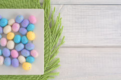 Easter egg candy on Square Dish on Green Placemat on White Wood Boards as Background stock image