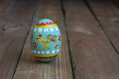 Easter egg with a cockerel on a wooden board.  Royalty Free Stock Photo