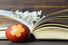 Easter egg colored with onion. Easter egg, spring flowers and open book. Easter egg colored with onion. Easter egg, spring flower branch and open book royalty free stock photography