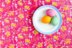 Easter egg on a colored table in the plate Royalty Free Stock Photos