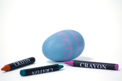 Easter Egg and Crayons. Colored Easter egg with matching crayons in foreground all isolated on a white background. Iamge has clipping path Royalty Free Stock Photos