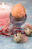 Easter egg in crystal cup, scattered quail eggs, spring red and pink small flowers, burning candle Stock Photography