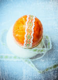 Easter egg in cup with ribbon on old blue textured background, vintage, top Stock Photo