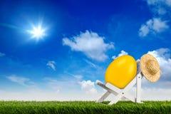 Easter egg on deck chair sun lounger in garden abstract funny concept blue sky background stock photos