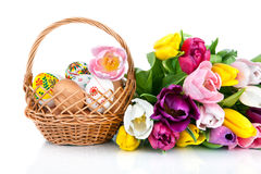 Easter egg decoration in basket and tulip flowers isolated on wh Stock Photos