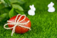 Easter egg dye with onion peel in red color on green grass backg. Easter egg dye with onion peel in red color close up on green grass background Royalty Free Stock Photo