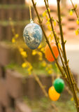 Easter egg Earth. An Easter egg as Earth globe hanging in a bush with yellow blossoms. The image has warm colors of spring time stock image