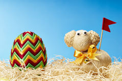 Easter egg and easter lamb in hay Stock Photos