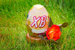 Easter egg and flower rose among the green grass. Stock Photos