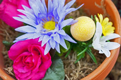 Easter egg in a flowerpot. Yellow sparkling easter egg in a flowerpot, artificial Royalty Free Stock Photography