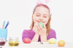 Small happy baby girl with easter eggs isolated on white royalty free stock images