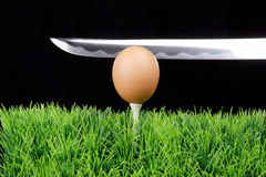 Easter egg on golf tee with sword Royalty Free Stock Image