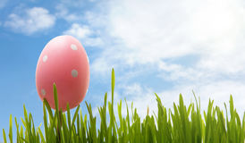 Easter egg and grass against blue sky Stock Image