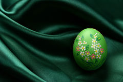 Easter egg green. A detail of a hand-painted Easter egg on dark green satin fabric Royalty Free Stock Images