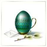 Easter egg with green ornament and sprig of willow. Easter egg with beautiful green geometric ornament on vintage metal stand with handle Royalty Free Stock Photography