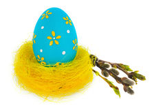 Easter egg hand painted in yellow bird`s nest with blooming twig Stock Photo