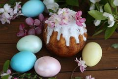 Easter egg in the hands of a child and a cake in sugar icing. Baby`s hands hold easter egg. Easter egg in the hands of a child. Easter egg in the hands of a royalty free stock photography