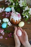 Easter egg in the hands of a child and a cake in sugar icing. Baby`s hands hold easter egg. Easter egg in the hands of a child. Easter egg in the hands of a stock photos