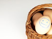 Easter egg with a happy face in the basket Stock Photos