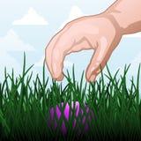 Easter egg hunt. Child's hand reaching for an Easter egg Stock Photo