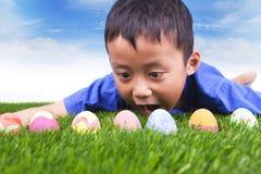 Easter egg hunt. Cute boy find easter eggs hidden in fresh green grass stock images