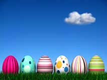 Easter Egg Hunt. 6 Easter Eggs in the grass with an out of focus beautiful blue sky background with a single cloud. See more variations in my Gallery Stock Photo