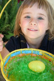 Easter Egg Hunt. A little girl holds her Easter basket with an egg she found in the Easter Egg hunt Royalty Free Stock Photos