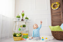 Easter egg hunt. Adorable child playing with Easter eggs at home Royalty Free Stock Images