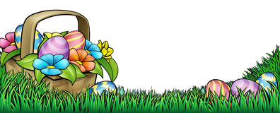 Easter Egg Hunt Background. An Easter background border frame footer of a basket hamper and Easter eggs in a spring field of grass and flowers Stock Photo