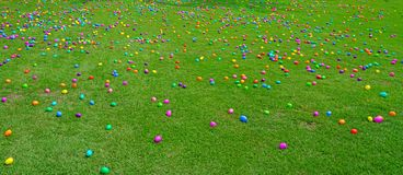 An Easter egg hunt with plastic eggs on a green lawn. An Easter egg hunt with colorful plastic eggs on a green lawn royalty free stock image