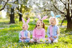 Easter egg hunt. Kids with bunny ears and basket. Royalty Free Stock Photos