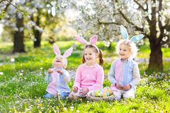 Easter egg hunt. Kids with bunny ears and basket. Stock Photos