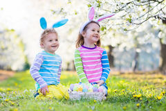 Easter egg hunt. Kids with bunny ears in spring garden. Kids on Easter egg hunt in blooming spring garden. Children with bunny ears searching for colorful eggs Stock Images