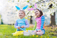 Easter egg hunt. Kids with bunny ears in spring garden. Royalty Free Stock Photo